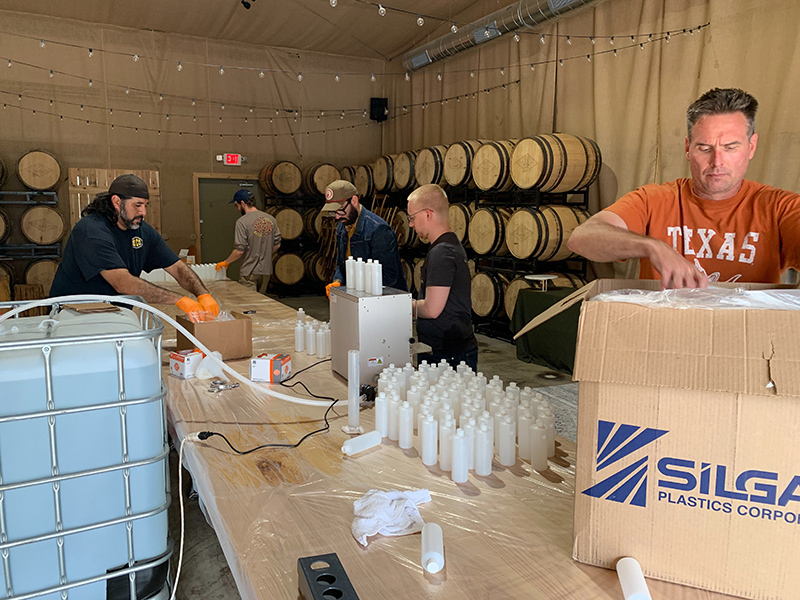 Desert Door Texas Sotol employees unpack materials and bottle hand sanitizer produced at their distillery in Driftwood, Texas.