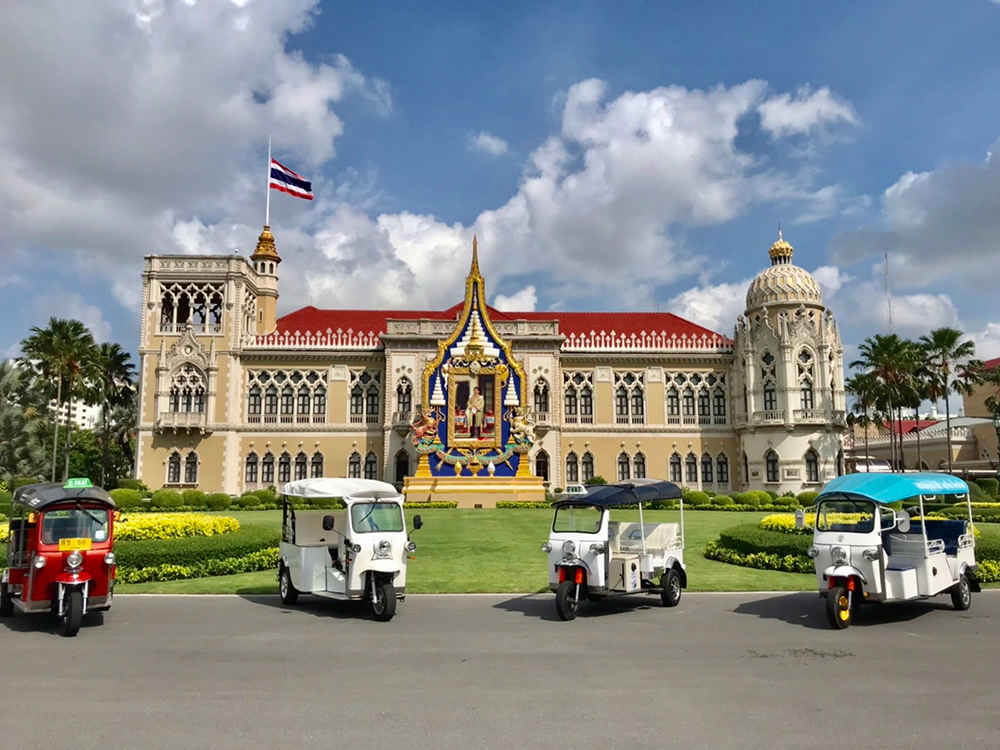 Front view of the Government House of Thailand, showcasing Thai Electric Tuk Tuk vehicles, manufactured in Thailand.
