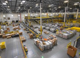 An Amazon warehouse where people and robots work together, in a safe environment.