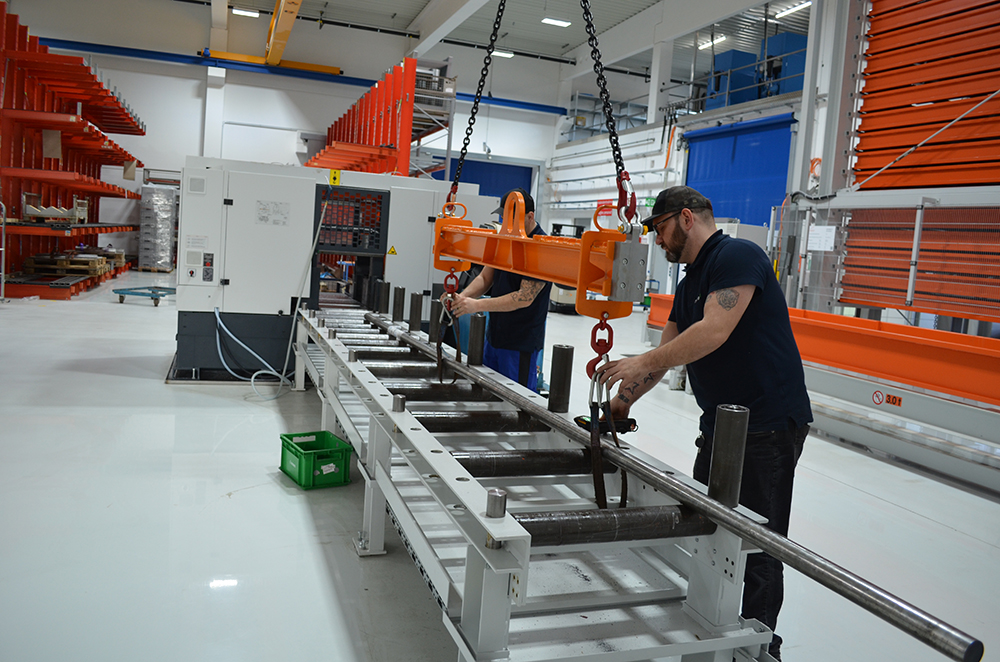 The employees then place the bar stock manually or by overhead crane on the magazine of one of the two saws.