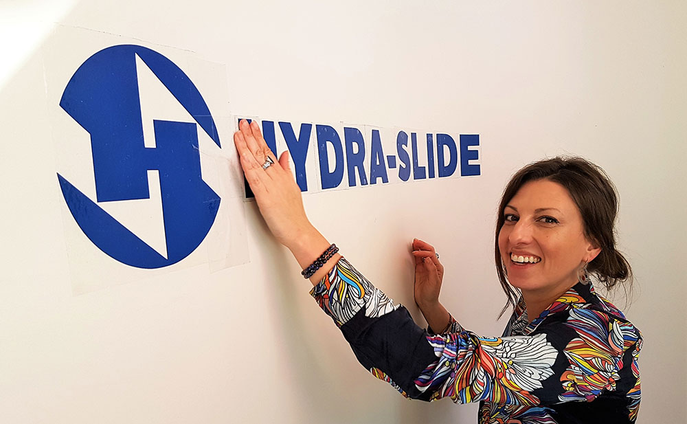 Janine Smith, vice president at Hydra-Slide, unveils the new logo.