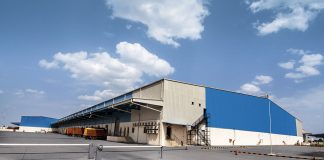 A large warehouse structure sits on a cement tarmac