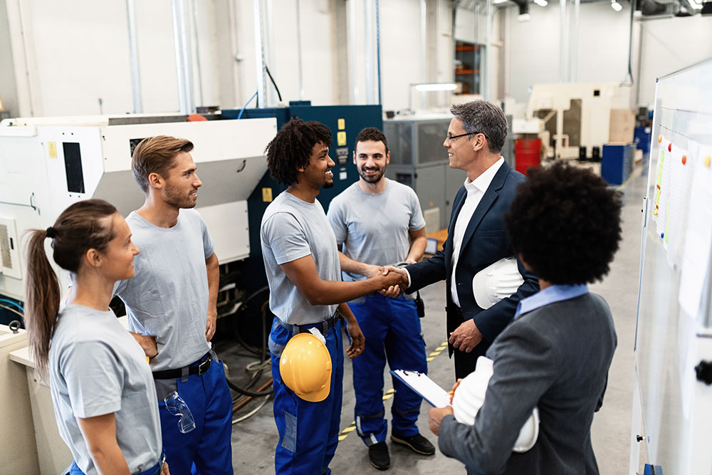 Company manager greeting with new manufacturing employees during a tour of factory. Credit: Drazen Zigic iStockphoto LP