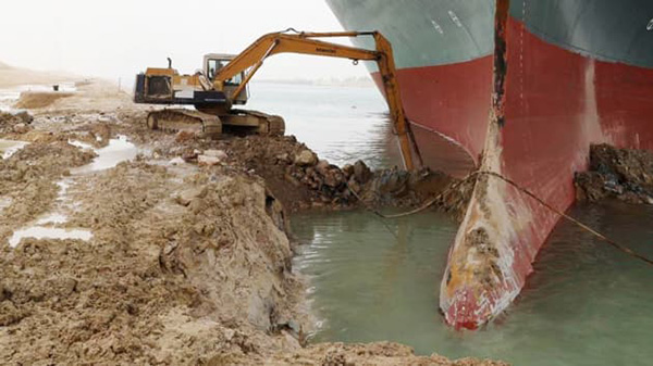 An excavator attempts to free Ever Given, one of the world's largest container ships after it ran aground, Suez Canal, Egypt March 25, 2021. (Image Source: Reuters, Suez Canal Authority)
